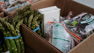 Asparagus and packaged food items are placed in a cardboard box.
