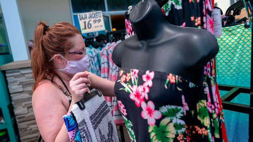 A woman looks at summer dresses outside a store on the boardwalk during the Memorial Day holiday weekend amid the coronavirus pandemic on May 23, 2020 in Ocean City, Maryland. - The beach front destination has lifted its COVID-19 related beach and boardwalk restrictions May 9 and lodging restrictions May 14. The state of Maryland moved from a stay-at-home order to safe-at-home order May 15. (Photo by Alex Edelman / AFP) (Photo by ALEX EDELMAN/AFP via Getty Images)