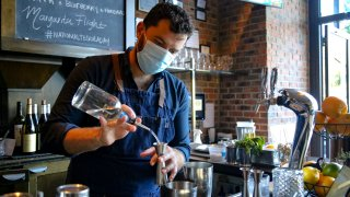 In this July 24, 2020, file photo, a bartender wearing a protective mask makes a drink at a restaurant in Chicago, Illinois.