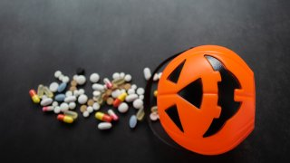 Plastic Pumpkin basket with colorful pills poured out from it.
