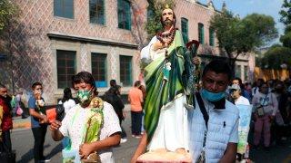 Fieles mexicanos cargan imágenes de San Judas Tadeo