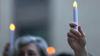 People hold up electric candles during a prayer vigil for victims of the coronavirus (COVID-19) pandemic.