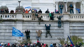 In this Jan. 6, 2021, file photo, supporters of then-resident Donald Trump climb the west wall of the the U.S. Capitol in Washington.