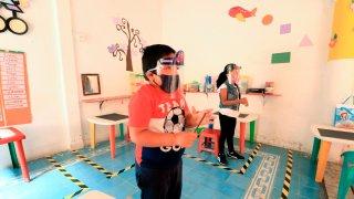 Dos niños con equipo de protección juegan en su salón de clases